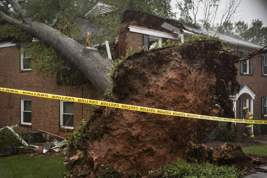 A Winston-Salem firefighter walks toward an apartment building which was struck by a toppled tree Thursday, Oct. 11, 2018, after the remnants of Hurricane Michael passed through Winston-Salem, N.C. (Allison Lee Isley/The Winston-Salem Journal via AP)