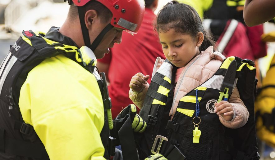 A member of the Winston-Salem Fire Department's water rescue team unzips the life jacket worn by Isabella Molina's, 5, after bringing her from an apartment complex to drier land Thursday, Oct. 11, 2018, after the remnants of Hurricane Michael passed through Winston-Salem, N.C. (Allison Lee Isley/The Winston-Salem Journal via AP)