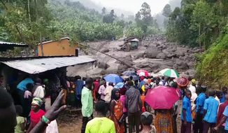 In this image made from video, residents look at a river filled with mud in Bududa District, Uganda, Friday, Oct. 12, 2018.  At least 30 people died in mudslides triggered by torrential rains in a mountainous area of eastern Uganda that is prone to such disasters, a Red Cross official said Friday. More victims were likely to be discovered when rescue reams access all the affected areas in the foothills of Mount Elgon, said Red Cross spokeswoman Irene Nakasiita. (AP Photo)