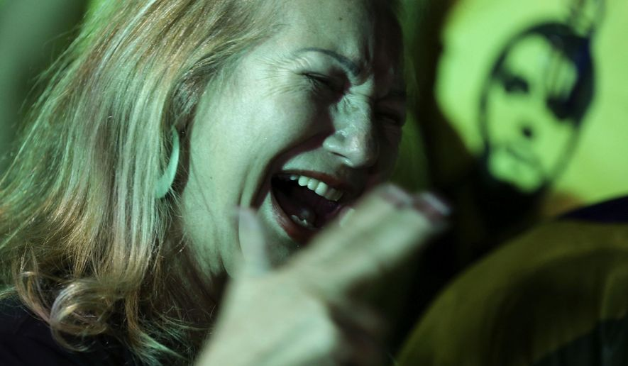 In this Sunday, Oct. 7, 2018 photo, a supporter of presidential frontrunner Jair Bolsonaro celebrates as she waits for election results, in front of the National Congress Palace, in Brasilia, Brazil. Brazilians appear on the cusp of handing the presidency to Bolsonaro, a brash former army captain who has reminisced fondly about dictatorship, pledged to jail corrupt politicians and promised an all-out war on the drugs and crime that plague South America's largest nation. (AP Photo/Eraldo Peres)