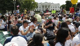 In this April 29, 2017, file photo, demonstrators sit on the ground along Pennsylvania Ave. in front of the White House in Washington. The National Park Service is exploring the question of whether it should recoup from protest organizers the cost of providing law enforcement and other support services for demonstrations held in the nation's capital. The proposed rule also could place new limits on spontaneous demonstrations and shrink a significant portion of the White House sidewalk accessible to the public. (AP Photo/Pablo Martinez Monsivais, File)