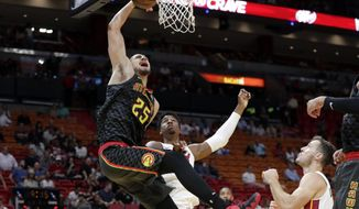 Atlanta Hawks' Alex Len (25) goes to the basket past Miami Heat's Hassan Whiteside, center, and Goran Dragic, right, during the first half of a preseason NBA basketball game, Friday, Oct. 12, 2018, in Miami. (AP Photo/Lynne Sladky)