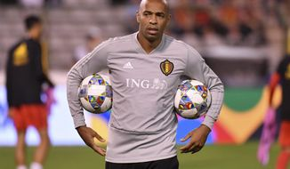 Belgium assistant coach Thierry Henry holds two balls during a warm up prior the UEFA Nations League soccer match between Belgium and Switzerland at the King Baudouin stadium in Brussels, Friday, Oct. 12, 2018. (AP Photo/Geert Vanden Wijngaert)
