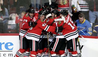 Chicago Blackhawks right wing Alex DeBrincat, center, celebrates with teammates after scoring in overtime against the St. Louis Blues during an NHL hockey game Saturday, Oct. 13, 2018, in Chicago. The Blackhawks won 4-3. (AP Photo/Nam Y. Huh)