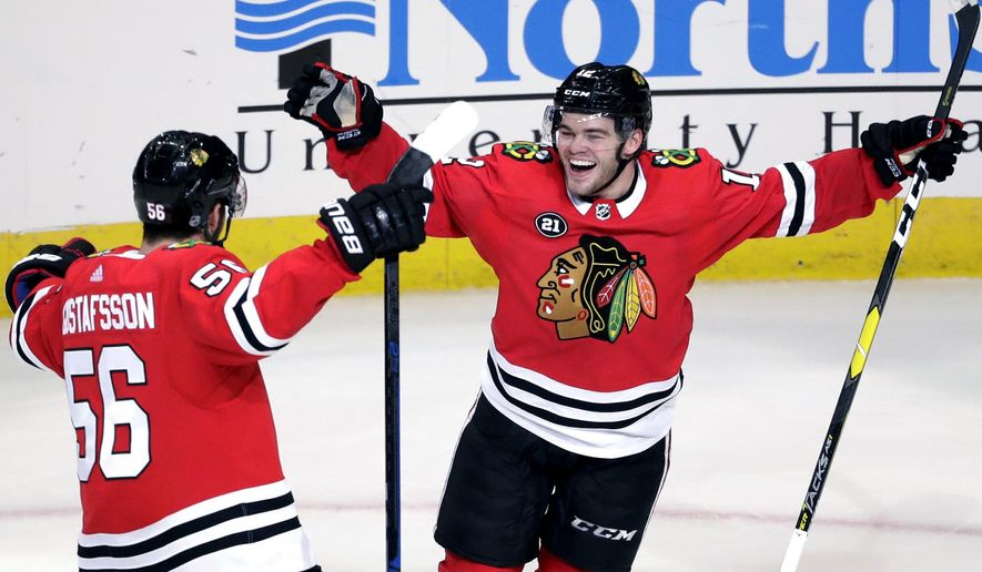 Chicago Blackhawks right wing Alex DeBrincat, right, celebrates with defenseman Erik Gustafsson after scoring against the St. Louis Blues during overtime in an NHL hockey game Saturday, Oct. 13, 2018, in Chicago. The Blackhawks won 4-3. (AP Photo/Nam Y. Huh)