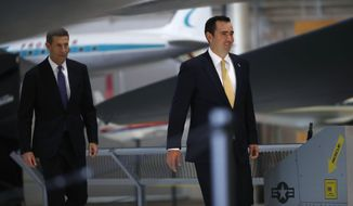FILE - In this July 11, 2018, file photograph, Republican nominee to run for Colorado's governorship, Walker Stapleton, right, leads his running mate, Lang Sias, into a news conference in a military aircraft museum in Denver. Stapleton, the state's treasurer for the past eight years, is facing U.S. Rep. Jared Polis, D-Colo., for the governor's office in the November election. (AP Photo/David Zalubowski, File)