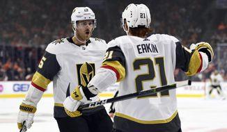 Vegas Golden Knights' Cody Eakin (21) celebrates with Jon Merrill after Eakin scored a goal during the third period of an NHL hockey game on Philadelphia Flyers goaltender Brian Elliott, Saturday, Oct. 13, 2018, in Philadelphia. The Golden Knights won 1-0. (AP Photo/Derik Hamilton)