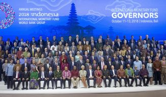 International Monetary Fund (IMF) governors gather for a group photo during the IMF and World Bank meetings in Bali, Indonesia on Saturday, Oct. 13, 2018. (AP Photo/Firdia Lisnawati)