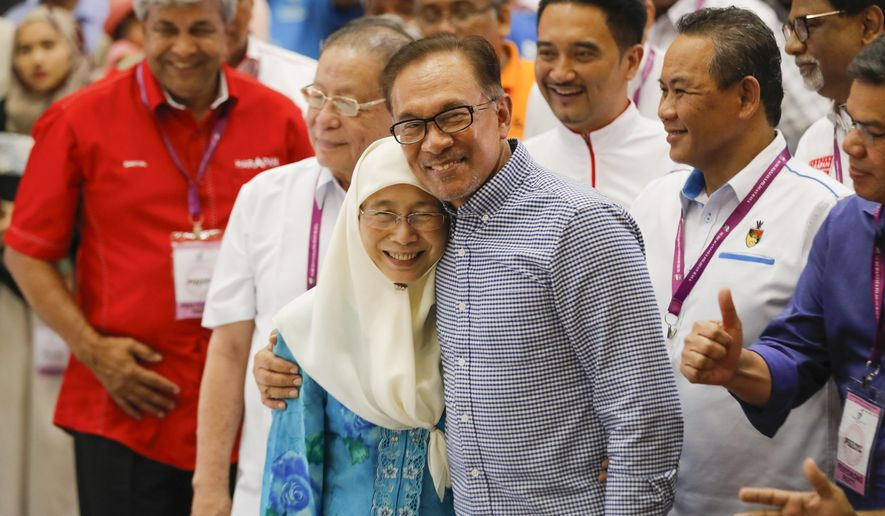 Malaysia's politician Anwar Ibrahim, right, hug his wife while Deputy Prime Minister Malaysia Wan Azizah Ismail celebrates after winning the by election in the southern coastal town in Port Dickson, Saturday, Oct. 13, 2018. Malaysian politician Anwar Ibrahim won a parliamentary seat and returns to active politics as he prepare for his eventual takeover from Prime Minister Mahathir Mohamad. (AP Photo/Vincent Thian)