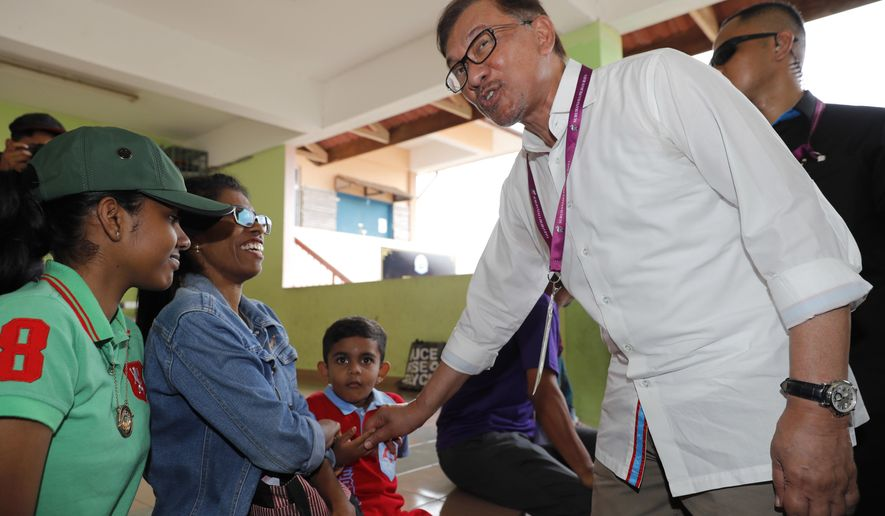 Malaysian politician Anwar Ibrahim, right, greets voters at a polling station in the southern coastal town of Port Dickson, where Anwar is vying for a seat along with six other candidates, Saturday, Oct. 13, 2018. Voting opened Saturday in a by-election that is expected to see charismatic Malaysian politician Anwar Ibrahim win a parliamentary seat and return to active politics as he prepare for his eventual takeover from Prime Minister Mahathir Mohamad. (AP Photo/Vincent Thian)