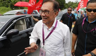 Malaysian politician Anwar Ibrahim, center, visits a polling station in the southern coastal town of Port Dickson, where Anwar is vying for a seat along with six other candidates, Saturday, Oct. 13, 2018. Voting opened Saturday in a by-election that is expected to see charismatic Malaysian politician Anwar Ibrahim win a parliamentary seat and return to active politics as he prepare for his eventual takeover from Prime Minister Mahathir Mohamad. (AP Photo/Vincent Thian)