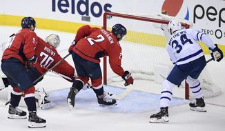 Toronto Maple Leafs center Auston Matthews (34) scores a goal against Washington Capitals defenseman Dmitry Orlov (9), of Russia, Matt Niskanen (2) and goaltender Braden Holtby (70) during the third period of an NHL hockey game, Saturday, Oct. 13, 2018, in Washington. The Maple Leafs won 4-2. (AP Photo/Nick Wass)