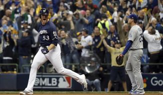 Milwaukee Brewers' Brandon Woodruff (53) celebrates after hitting a home run during the third inning of Game 1 of the National League Championship Series baseball game against the Los Angeles Dodgers Friday, Oct. 12, 2018, in Milwaukee. (AP Photo/Jeff Roberson)