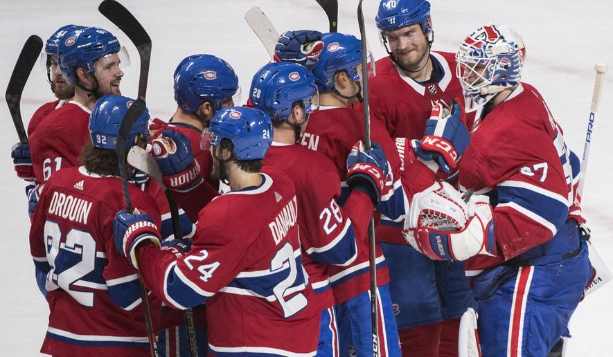 Players from the Montreal Canadiens celebrate after defeating the Pittsburgh Penguins in an NHL hockey game, Saturday, Oct. 13, 2018 in Montreal.  (Graham Hughes/Canadian Press via AP)