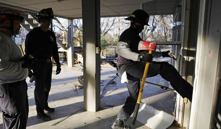 Members of a South Florida urban search and rescue team try to gain entry to a home while looking for survivors of hurricane Michael in Mexico Beach, Fla., Friday, Oct. 12, 2018. (AP Photo/David Goldman)