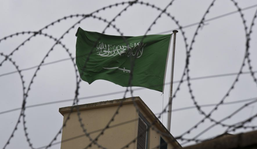 A flag of Saudi Arabia flies behind barb wire, on the roof top of Saudi Arabia's consulate in Istanbul, Saturday, Oct. 13, 2018.  Turkish officials have an audio recording of the alleged killing of journalist Jamal Khashoggi from the Apple Watch he wore when he walked into the Saudi Consulate in Istanbul over a week ago, a pro-government Turkish newspaper reported Saturday. (AP Photo/Petros Giannakouris)