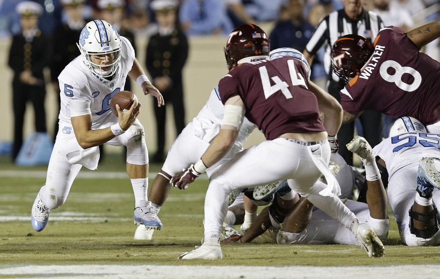 North Carolina quarterback Cade Fortin (6) runs the ball while Virginia Tech's Dylan Rivers (44) looks to tackle him during the first half of an NCAA college football game in Chapel Hill, N.C., Saturday, Oct. 13, 2018. (AP Photo/Gerry Broome)