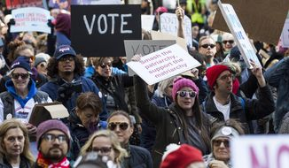 Demonstrators marched through the streets of Chicago during the Women's March Chicago on Saturday, Oct. 13, 2018.  Thousands of people marched through downtown Chicago to express their displeasure at President Donald Trump and encourage voters to go to the polls for next month's midterm election.  (Ashlee Rezin/Chicago Sun-Times via AP)