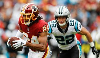 Washington Redskins cornerback Josh Norman (24) carries the ball after pulling in an interception as Carolina Panthers running back Christian McCaffrey (22) pursues him during the first half of an NFL football game, Sunday, Oct. 14, 2018, in Landover, Md. (AP Photo/Patrick Semansky)