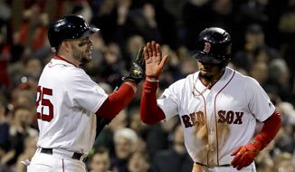 Boston Red Sox's Mookie Betts celebrates after scoring on a passes by with Steve Pearce during the fifth inning in Game 2 of a baseball American League Championship Series against the Houston Astros on Sunday, Oct. 14, 2018, in Boston. (AP Photo/David J. Phillip)