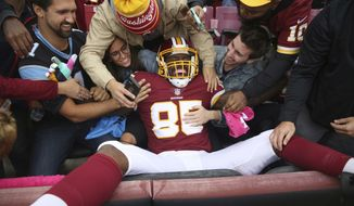 Washington Redskins tight end Vernon Davis (85) celebrates with fans after this touchdown catch during the first half of an NFL football game against the Carolina Panthers, Sunday, Oct. 14, 2018, in Landover, Md. (AP Photo/Pablo Martinez Monsivais)