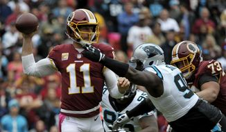 Washington Redskins quarterback Alex Smith (left) throws the ball while being rushed by Carolina Panthers defensive tackle Kawann Short (right) during an NFL football game between the Carolina Panthers and Washington Redskins, Sunday, Oct. 14, 2018, in Landover, Md. (AP Photo/Mark Tenally) ** FILE **