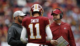 Washington Redskins quarterback Alex Smith speaks with head coach Jay Gruden, right, during an NFL football game against the Carolina Panthers, Sunday, Oct. 14, 2018 in Landover, Md. (AP Photo/Patrick Semansky) **FILE**