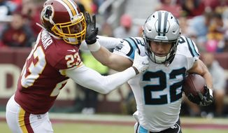 Carolina Panthers running back Christian McCaffrey (22) carries the ball past Washington Redskins cornerback Quinton Dunbar (23) during the second half of an NFL football game, Sunday, Oct. 14, 2018, in Landover, Md. (AP Photo/Pablo Martinez Monsivais)