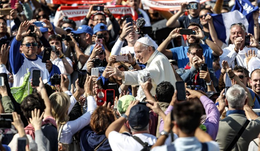 """Pope Francis waves to faithful as he leaves St. Peter's Square at the Vatican, Sunday, Oct. 14, 2018. Pope Francis has declared Pope Paul VI and slain Salvadoran Archbishop Oscar Romero saints, reciting in Latin the rite of canonization at the start of Mass in St. Peter's Square. After hearing brief biographies of Paul, Romero and five other people canonized Sunday, Francis declared them saints and """"decreed that they are to be venerated as such by the whole church."""" (Giuseppe Lami/ANSA via AP)"""