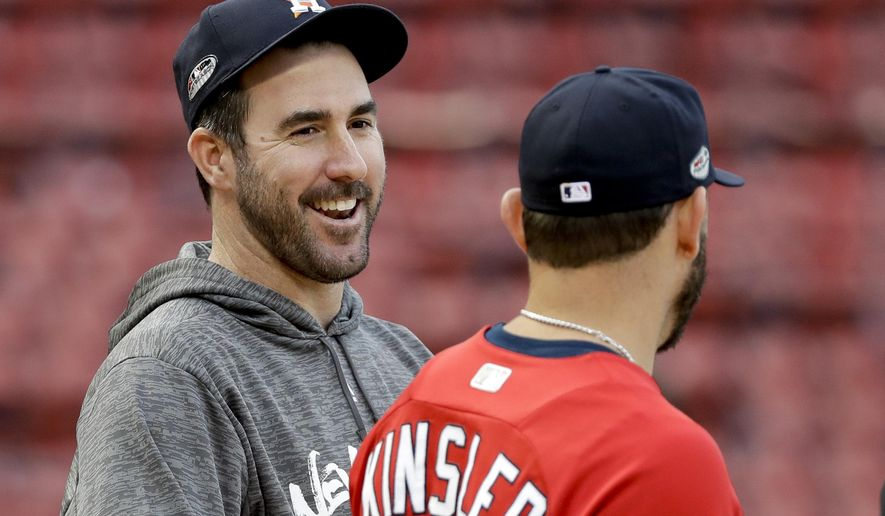 Houston Astros starting pitcher Justin Verlander, left, laughs with Boston Red Sox second baseman Ian Kinsler during batting practice before Game 2 of a baseball American League Championship Series on Sunday, Oct. 14, 2018, in Boston. (AP Photo/David J. Phillip)