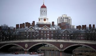 FILE - In this March 7, 2017 file photo, rowers paddle down the Charles River past the campus of Harvard University in Cambridge, Mass. A lawsuit alleging racial discrimination against Asian American applicants in Harvard's admissions process is heading to trial in Boston's federal court on Monday, Oct. 15, 2018. Harvard denies any discrimination, saying it considers race as one of many factors when considering applicants. (AP Photo/Charles Krupa, File)