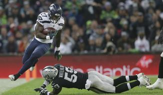 Seattle Seahawks running back Mike Davis (27), left, escapes the clutches of Oakland Raiders linebacker Tahir Whitehead (59) during the first half of an NFL football game at Wembley stadium in London, Sunday, Oct. 14, 2018. (AP Photo/Tim Ireland)