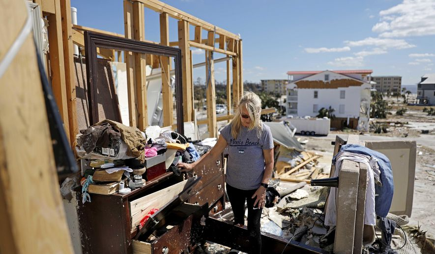 "Candace Phillips sifts through what was her third-floor bedroom while returning to her damaged home in Mexico Beach, Fla., Sunday, Oct. 14, 2018, in the aftermath of Hurricane Michael. ""We spent 25 years of our marriage working to get here and we're going to stay,"" said Phillips of her and husband's plans to rebuild. (AP Photo/David Goldman)"