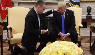 President Donald Trump prays with American pastor Andrew Brunson in the Oval Office of the White House, Saturday, Oct. 13, 2018, in Washington. Brunson returned to the U.S. around midday after he was freed Friday, from nearly two years of detention in Turkey. (AP Photo/Jacquelyn Martin)