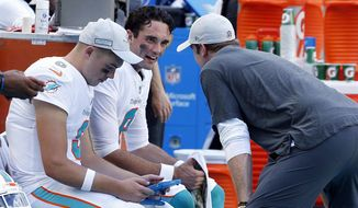 Miami Dolphins quarterback Brock Osweiler (8), talks to injured quarterback Ryan Tannehill, during the second half of an NFL football game against the Chicago Bears, Sunday, Oct. 14, 2018, in Miami Gardens, Fla. (AP Photo/Joel Auerbach)