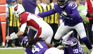 Arizona Cardinals quarterback Josh Rosen, left, is sacked by Minnesota Vikings defenders Anthony Harris (41), Mackensie Alexander (20) and Stephen Weatherly (91) during the first half of an NFL football game, Sunday, Oct. 14, 2018, in Minneapolis. (AP Photo/Bruce Kluckhohn)