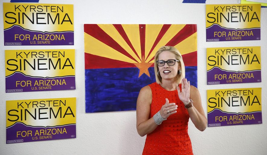 FILE - In this Aug. 28, 2018, file photo, Rep. Kyrsten Sinema, D-Ariz., talks to campaign volunteers at a Democratic campaign office in Phoenix. As the November elections near, Democrats are focusing on health care. It's been a constant drumbeat since the GOP launched its effort to repeal the Obama-era health law and is the subject of the greatest share of political ads on television now. It's a top issue in campaigns from Virginia to Nebraska to California, and especially in Arizona, where Democratic Rep. Kyrsten Sinema has made it the foundation of her Senate campaign. (AP Photo/Ross D. Franklin, File)