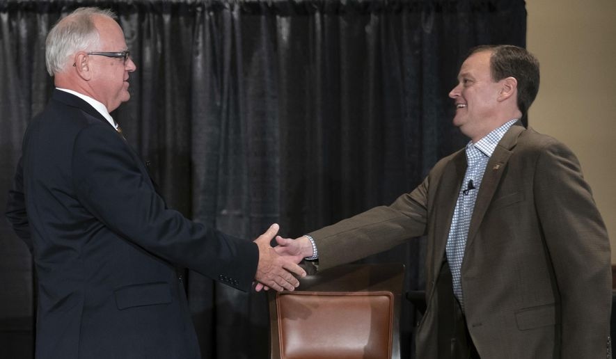FILE - In this Aug. 17, 2018 file photo, candidates for Minnesota governor, Democrat Tim Walz and Republican Jeff Johnson shake hands at the beginning of their first debate at Grand View Lodge, Nisswa, Minn. Amid big health care campaign promises, Minnesota's next governor will be tasked with fixing a math problem: How can the state continue covering its existing programs. Walz and Johnson will weigh the fate of a provider tax that helps cover more than 1 million Minnesotans but is set to expire. (Glen Stubbe /Star Tribune via AP File)