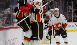Calgary Flames left wing Johnny Gaudreau (13) leaps into center Sean Monahan's arms after Gaudreau scored in overtime of an NHL hockey game against the Colorado Avalanche on Saturday, Oct. 13, 2018, in Denver. Calgary won 3-2. (AP Photo/Joe Mahoney)