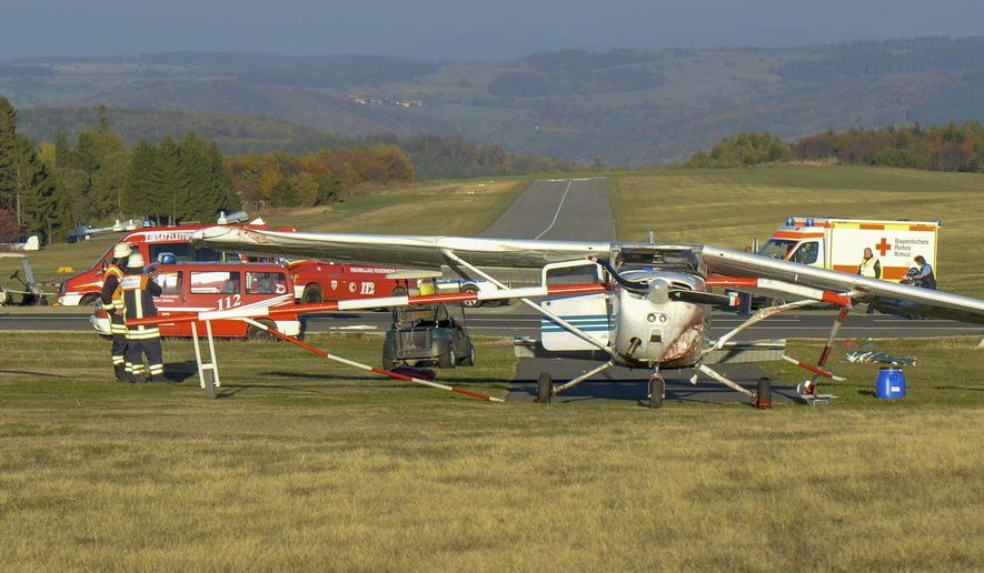 Firefighters stand beside a light aircraft near the airport in Gersfeld, Germany, Sunday, Oct. 14, 2018 after  three people died after they were hit by the small plane as it attempted to take off from an aborted landing. (Martin Engel/Osthessen-News/dpa via AP)