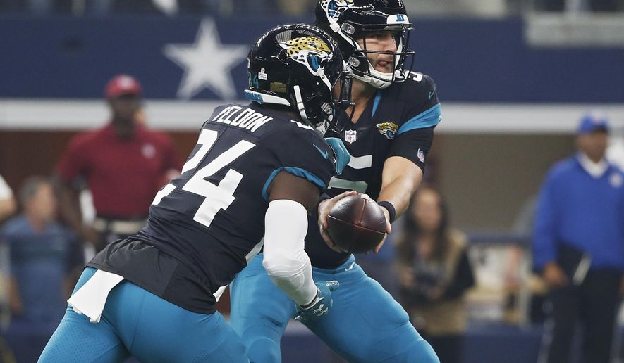 Jacksonville Jaguars quarterback Blake Bortles, right, hands off to running back T.J. Yeldon (24) in the first half of an NFL football game against the Dallas Cowboys in Arlington, Texas, Sunday, Oct. 14, 2018. (AP Photo/Ron Jenkins)