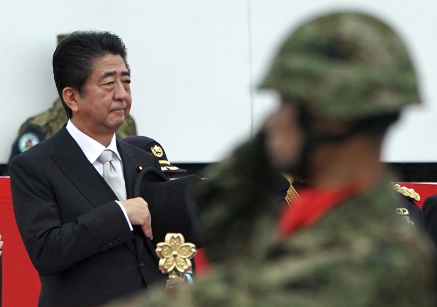 Japanese Prime Minister Shinzo Abe, center standing, reviews members of Japan Self-Defense Forces (SDF) marching during the Self-Defense Forces Day at Asaka Base in Asaka, north of Tokyo, Sunday, Oct. 14, 2018. Abe renewed his pledge to push for a revision to Japan's war-renouncing constitution at an annual defense review. (AP Photo/Eugene Hoshiko)