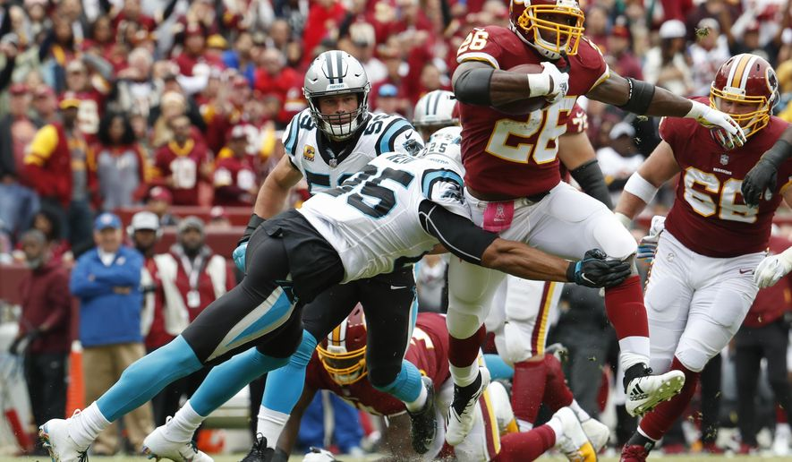842839972 Washington Redskins running back Adrian Peterson (26) is stopped by  Carolina Panthers safety Eric