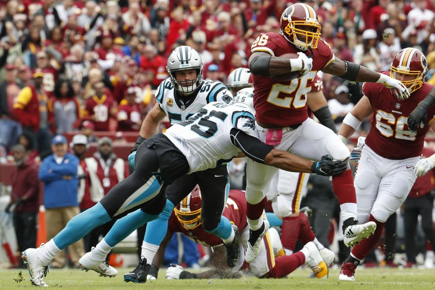 Washington Redskins running back Adrian Peterson (26) is stopped by Carolina Panthers safety Eric Reid (25) during the first half of an NFL football game, Sunday, Oct. 14, 2018, in Landover, Md. (AP Photo/Pablo Martinez Monsivais)