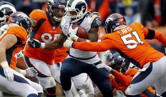Los Angeles Rams running back Todd Gurley (30) runs as Denver Broncos linebacker Todd Davis (51) and defensive end Derek Wolfe (95) defend during the second half of an NFL football game, Sunday, Oct. 14, 2018, in Denver. (AP Photo/Joe Mahoney)