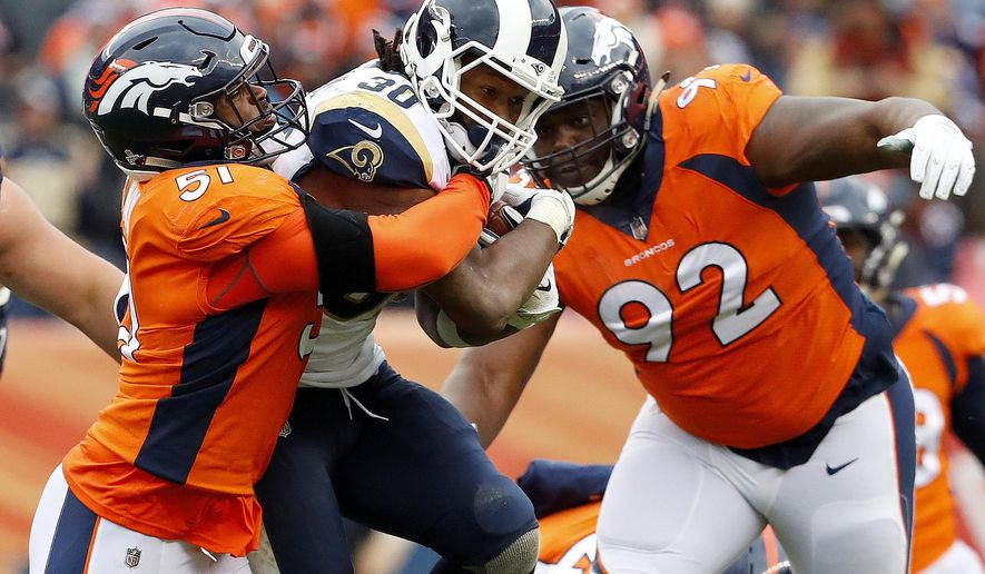 Los Angeles Rams running back Todd Gurley (30) is hit by Denver Broncos defensive end Zach Kerr (92) and linebacker Todd Davis (51) during the second half of an NFL football game, Sunday, Oct. 14, 2018, in Denver. (AP Photo/Joe Mahoney)