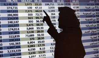 """FILE - In this Oct. 7, 2008 file photo, the shadow of a Saudi trader is seen on a stock market monitor in Riyadh, Saudi Arabia. The Saudi stock market sharply fell Sunday after President Donald Trump threatened """"severe punishment"""" over the disappearance of Washington Post contributor Jamal Khashoggi. (AP Photo/Hassan Ammar, File)"""