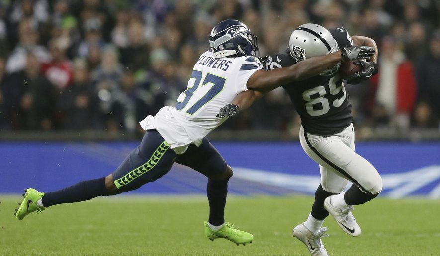 Seattle Seahawks cornerback Tre Flowers (37) tackles Oakland Raiders wide receiver Amari Cooper (89) during the first half of an NFL football game at Wembley stadium in London, Sunday, Oct. 14, 2018. (AP Photo/Tim Ireland)
