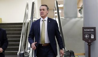 FILE - In this Thursday, Oct. 4, 2018, file photo, Sen. David Perdue, R-Ga., arrives on Capitol Hill, in Washington. A Georgia Tech political group says Perdue snatched a phone from a student who was video recording while asking the Republican lawmaker a question about Georgia's governor's race. In a statement, a Perdue spokesperson said the senator thought he was being asked to take a picture, so he grabbed the phone to take a selfie. (AP Photo/Alex Brandon, File)