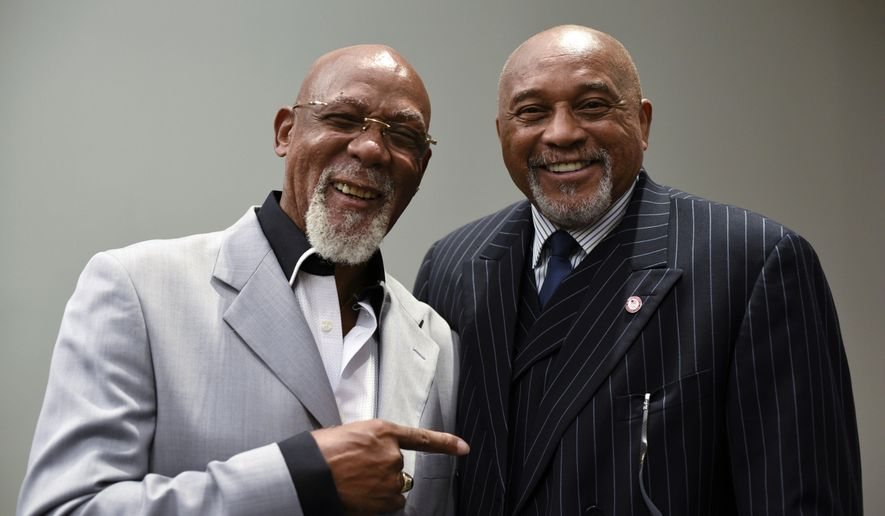FILE - In this Sept. 28, 2016, file photo, John Carlos, left, and Tommie Smith pose for a portrait at Georgetown University in Washington. When Smith and Carlos raised their fists 50 years ago at the Mexico City Olympics, they had a captive audience, back in the age when TV was king and the entire audience was rapt. A half-century later, many of the messages our athletes disseminate are every bit as powerful, but the audience is much more distracted. (AP Photo/Sait Serkan Gurbuz, File)